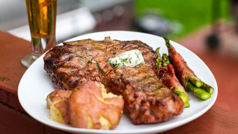 Porterhouse alla griglia con burro all'aglio e prezzemolo. Ricetta barbecue.