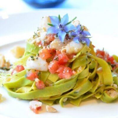 Tagliatelle verdi con sugo di baccalà, mandorle, pomodori ed erbe aromatiche ricetta pasta fresca